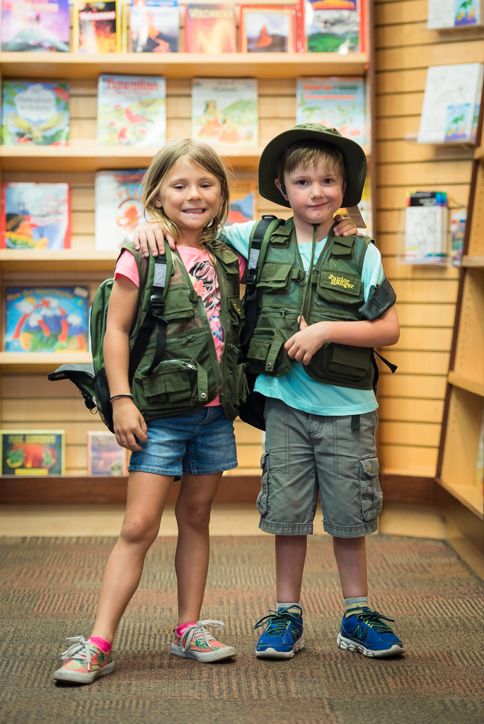 Photograph of a young boy and girl trying on kids' ranger gear in a National Park gift shop.