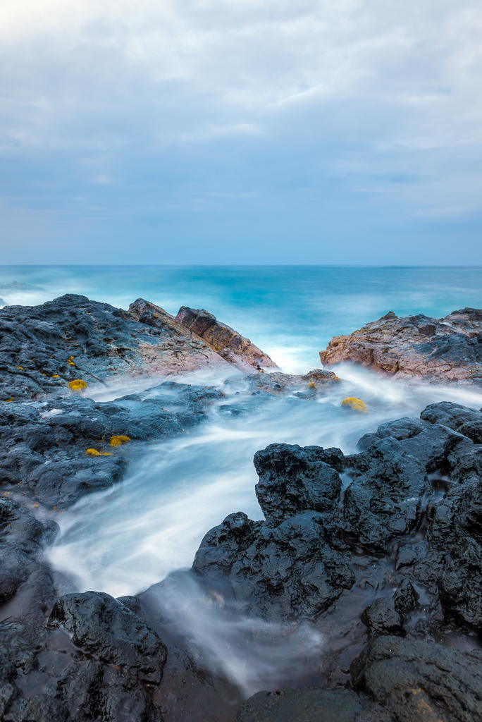 Long exposure of a wave crashing against a shore of volcanic rock in Kailua-Kona.