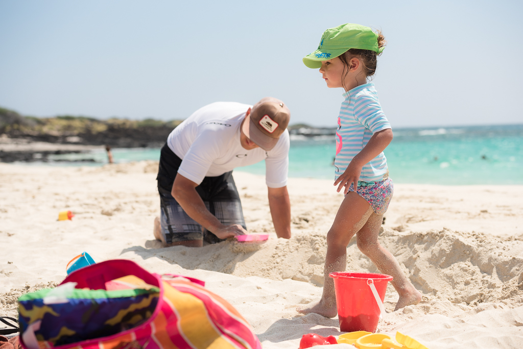 Photograph of a father digging in the sand at a beach while his young daughter walks on by.