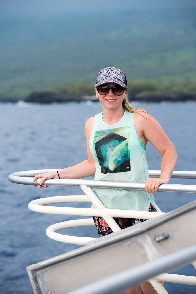 A young woman stands at the bow of a snorkeling boat of the coast of Hawaii's Big Island