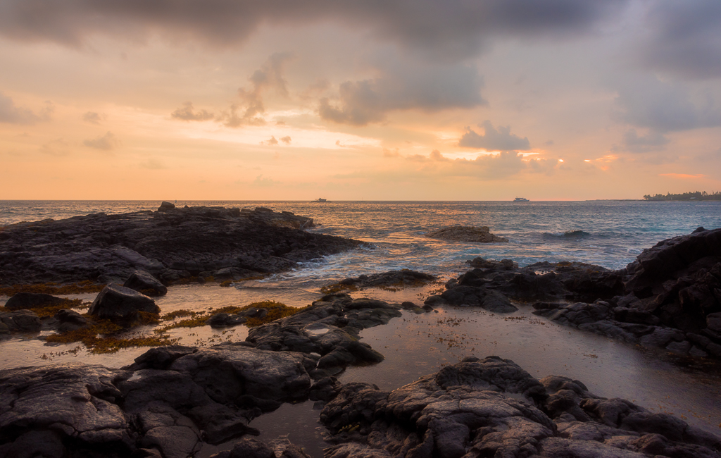 A sunset landscape photo during a rainy evening on the shoreline of Kailua-Kona on the Big Island of Hawaii.