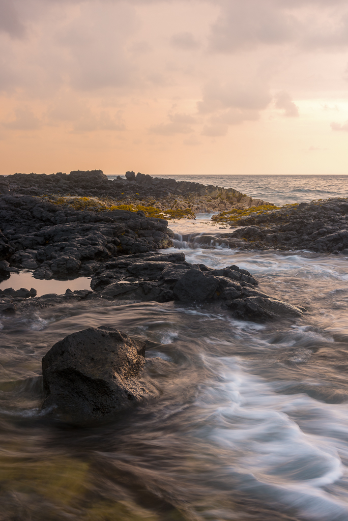 A long exposure landscape photograph of waves washing up against rocky shoals in Kailua-Kona.