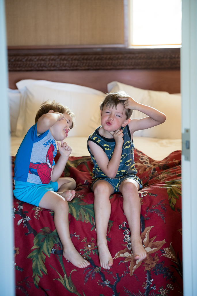 Two boys in superhero pajamas goof around on a bed on vacation.