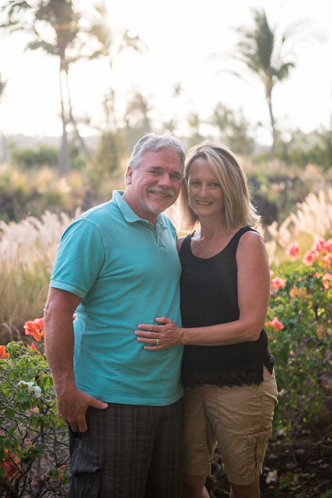 A portrait photograph of a husband and wife standing in a garden in Hawaii.