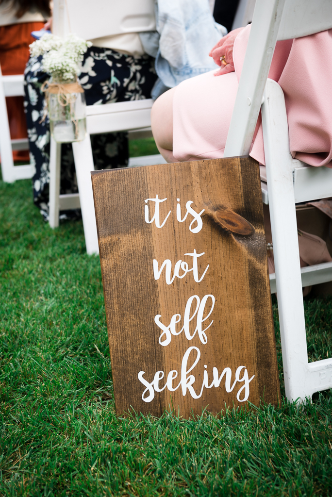 A wooden sign plate quotes biblical scripture from 1 corinthians at a wedding.