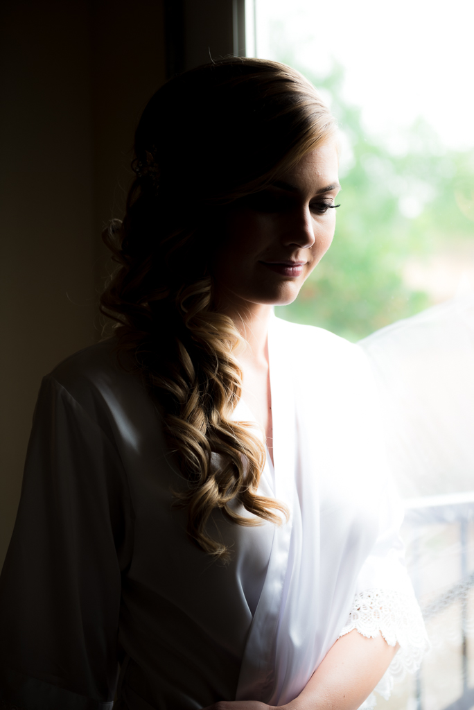 Photograph of a bride looking away from the camera, wearing a white robe.