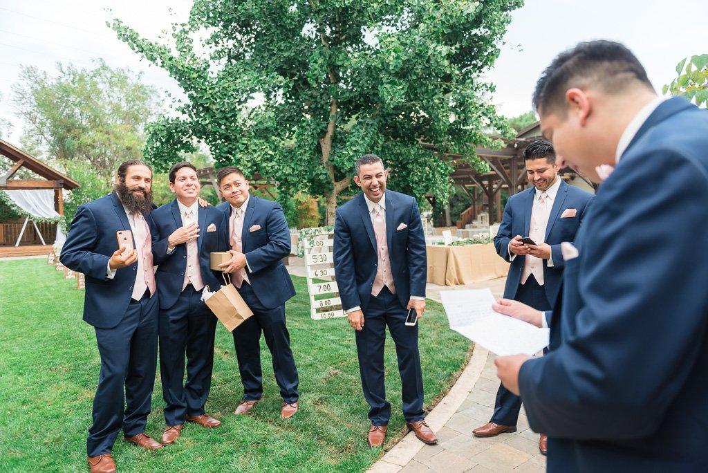 Photograph of groomsmen joking with the groom.