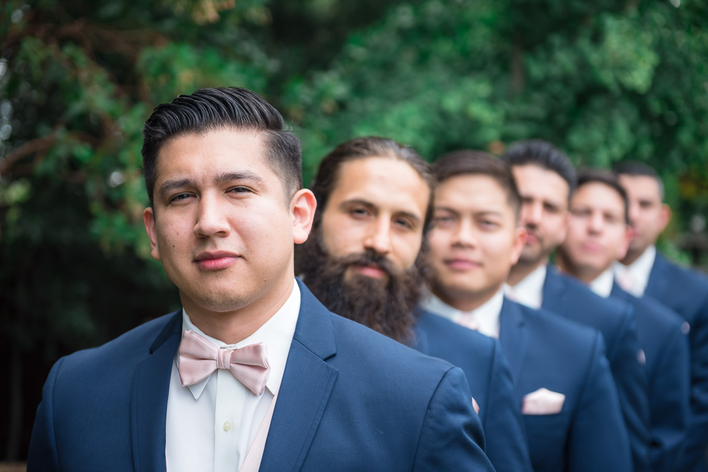 A groom in a blue tux stands in focus while his groomsmen stand out of focus behind him.