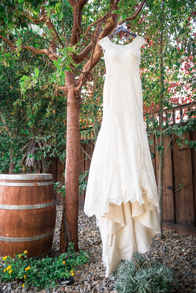 Photograph of a wedding dress hanging from a tree, near a barrel