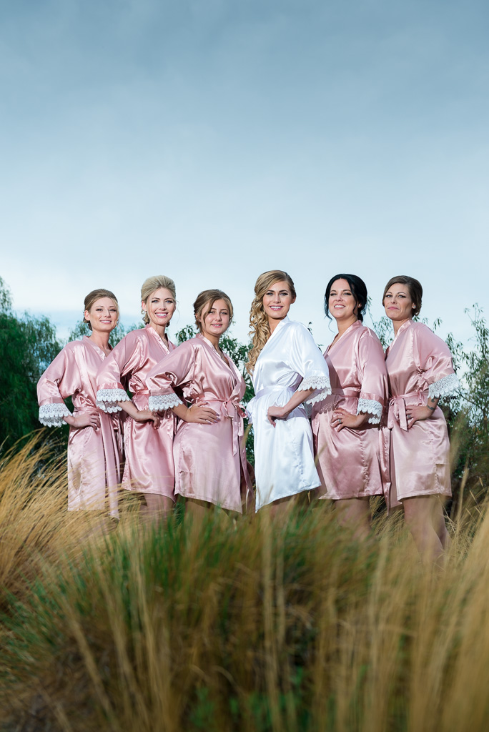 A dramatic outdoor photo of a bride and bridemaid in matching robes.