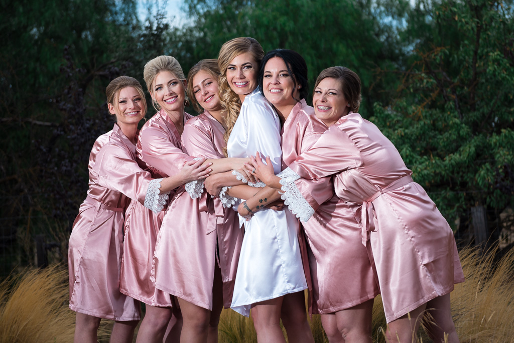 Group photograph of a bridal party wearing matching robes.