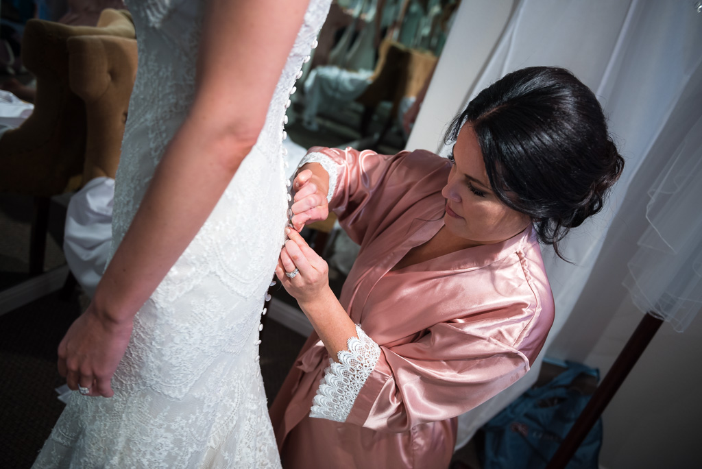 A bridesmaid helps a bride finish putting on her dress.