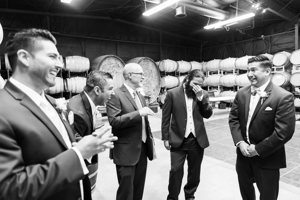 Black and white photograph of a wedding officiant joking with a groom and his groomsmen.