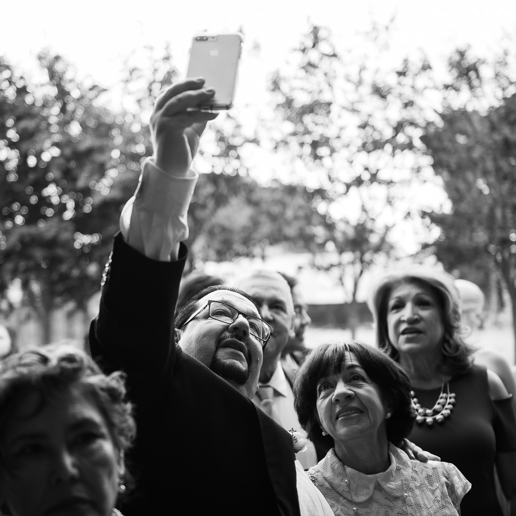 Black and white photograph of the father of the groom taking a selfie at a wedding.