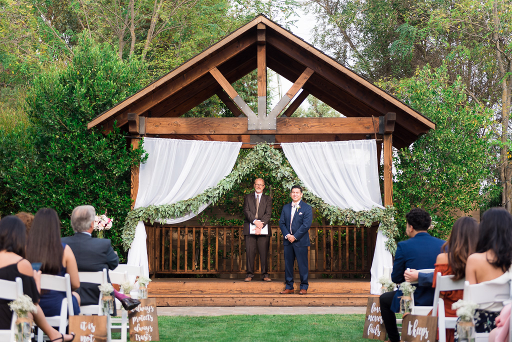 Photograph of the groom and officiant standing at the Crooked Vine Winery courtyard.