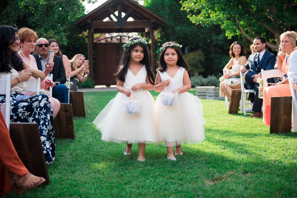 Two flower girls walk down the aisle just before the ceremony.