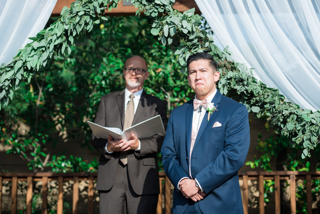 Photograph of a latino groom taking his first look at his bride.