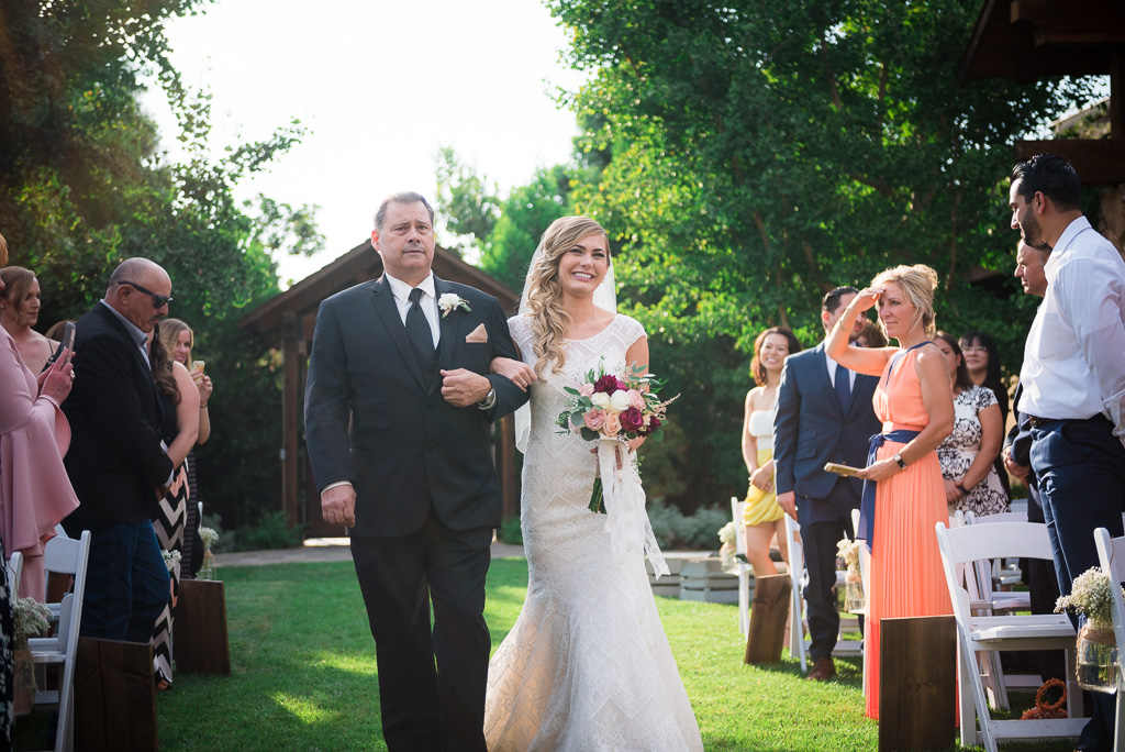 Photograph of a bride walking down the aisle with her father.