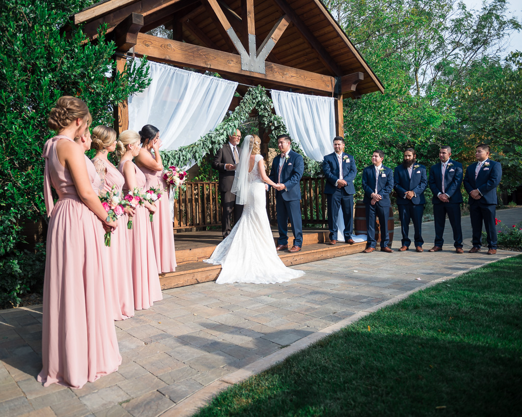 Photograph of an entire bridal party observing a bride and groom exchanging vows.