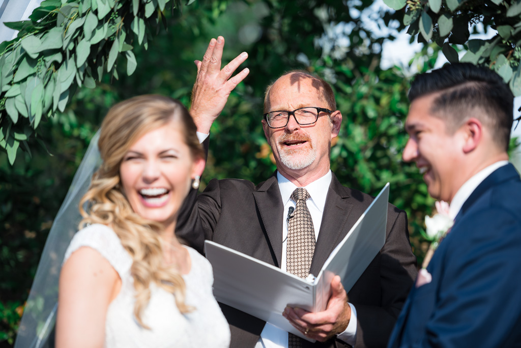 Photograph of an officiant making a bride and groom smile during their wedding ceremony.