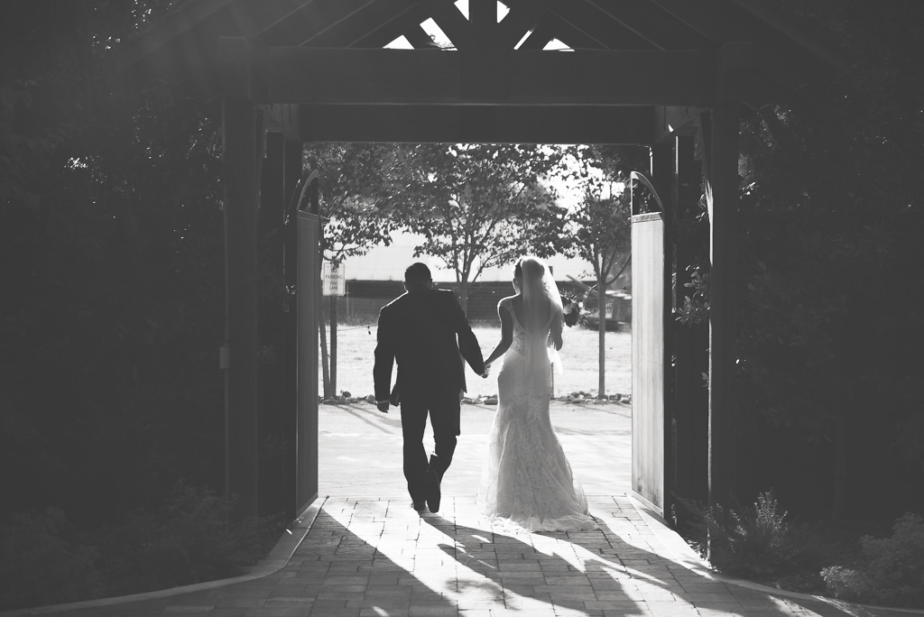 A black and white photograph of a bride and groom walking out of their wedding ceremony.