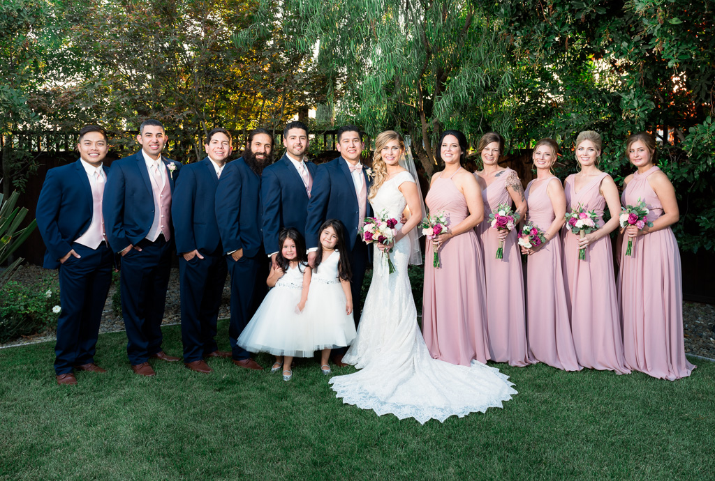 A bridal party photo featuring blue tuxedos and pink dresses.