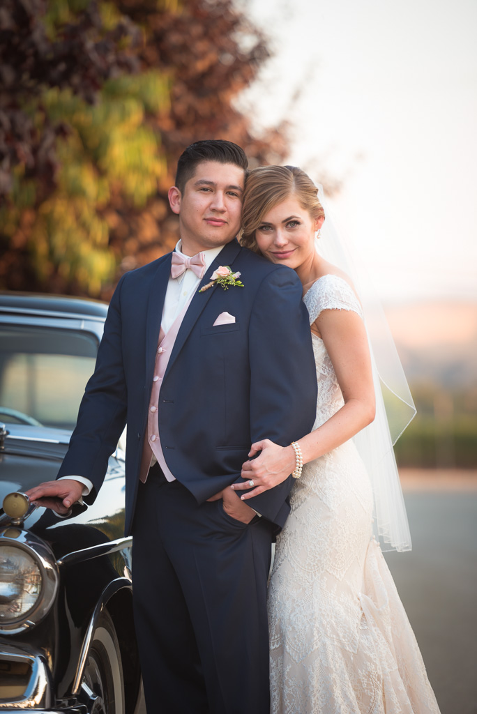 A bride and groom pose against an old Studebaker automobile at sunset.