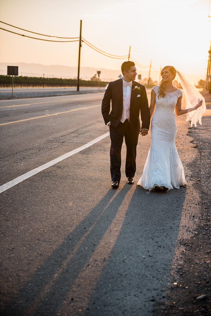 A bride and groom talk and laugh by the side of the road.