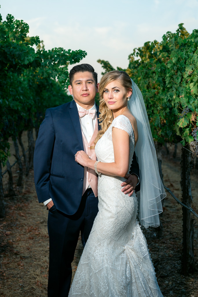 Close up of a bride and groom standing amongst grapevines in a Livermore, CA vineyard.