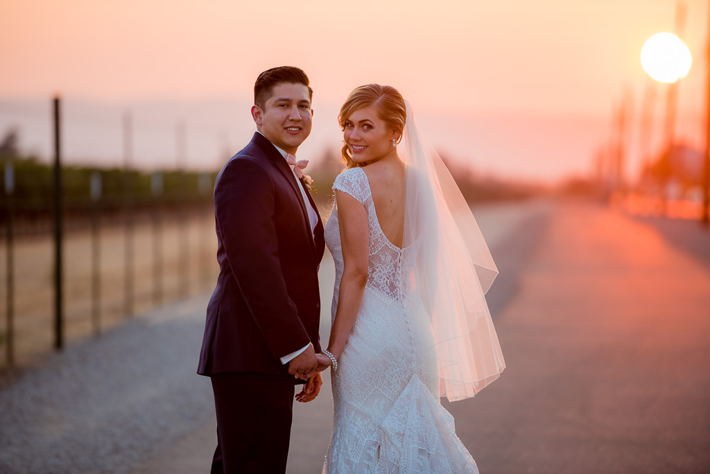 A natural light portrait of a bride and groom walking by a vineyard at sunset.