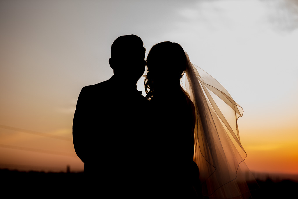 A silhouetted photo of a bride and groom at sunset, with veil blowing.