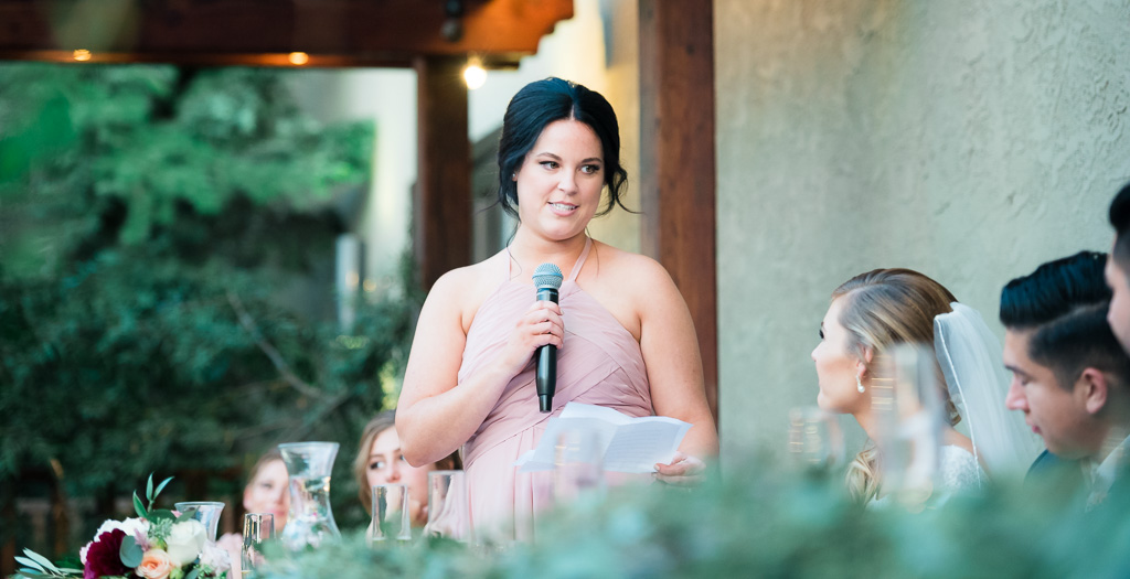Photograph of a matron of honor delivering a toast at a wedding reception.