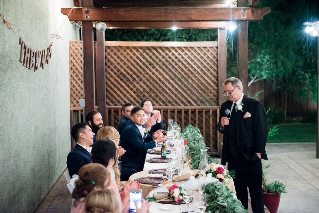 Photograph of a bride's father delivering a toast as the groom looks on.