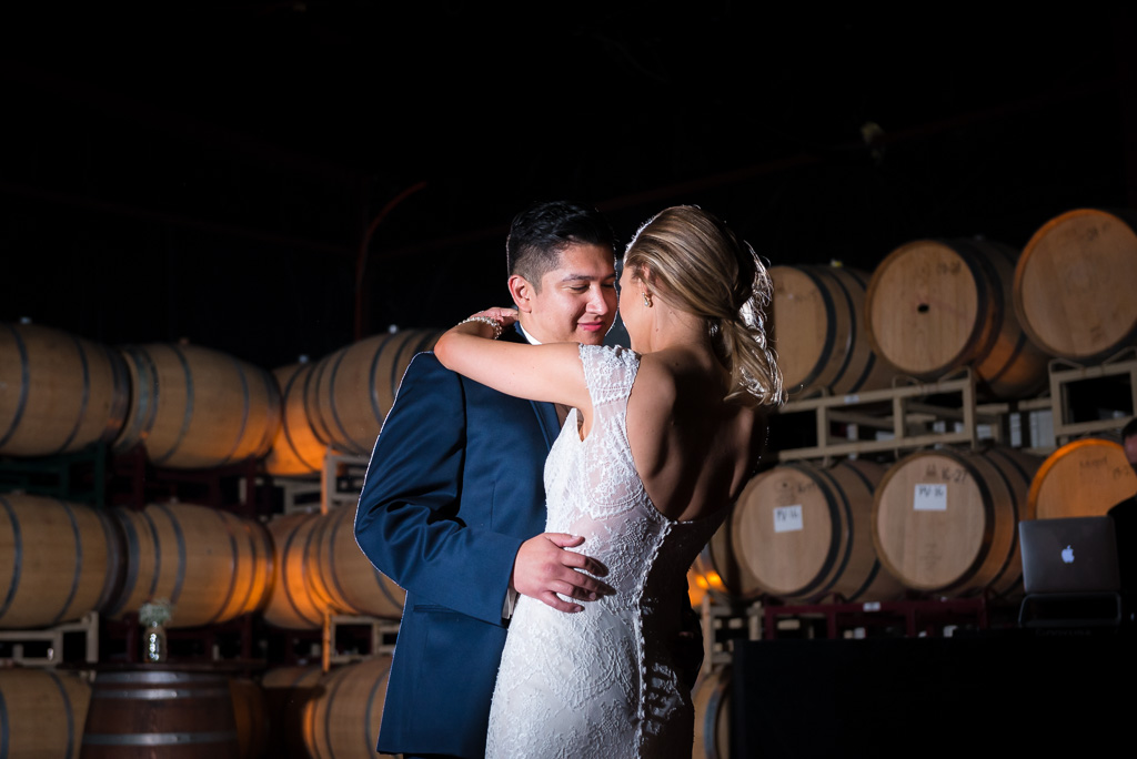 A bride and groom share their first dance in the barrel room of the Crooked Vine winery.