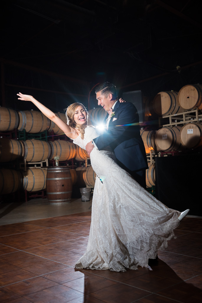 A groom dips his bride at the end of a first dance inside the Crooked Vine Winery Barrel Room.