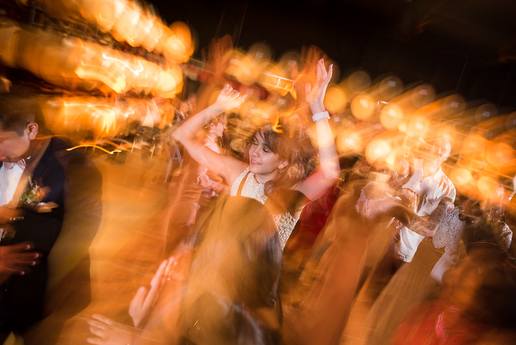 Motion-blurred photograph of a young woman dancing at a wedding.