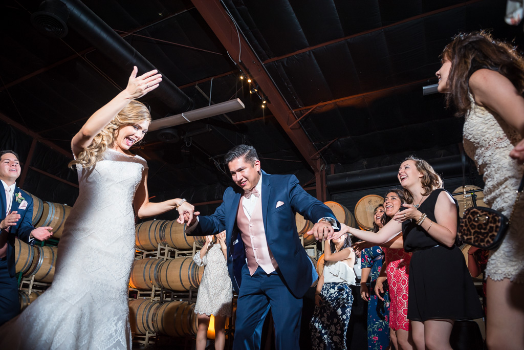 A bride and groom enjoy dancing with their guests at the Crooked Vine Winery Barrel Room.