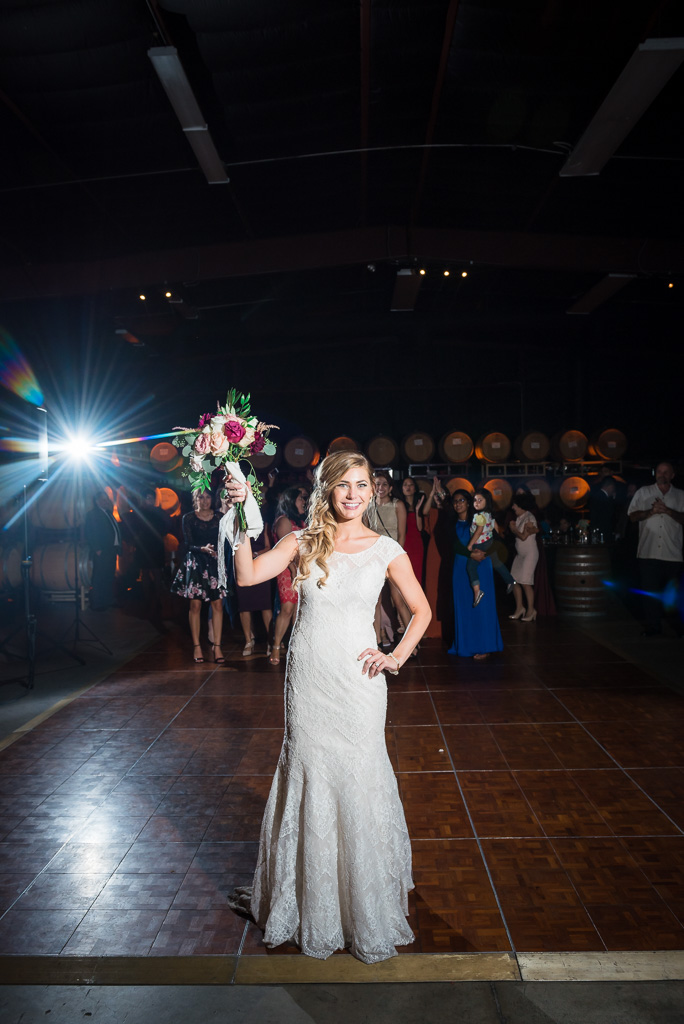 A bride prepares to throw her bouquet during the wedding reception.