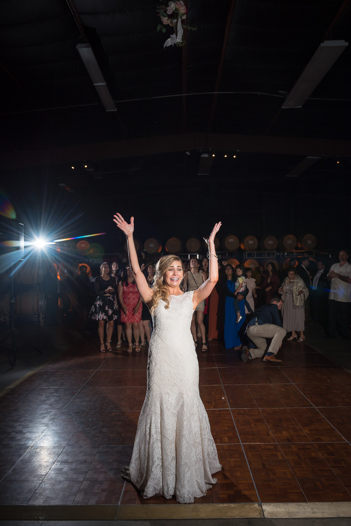 A bride tosses her bouquet at her wedding reception.