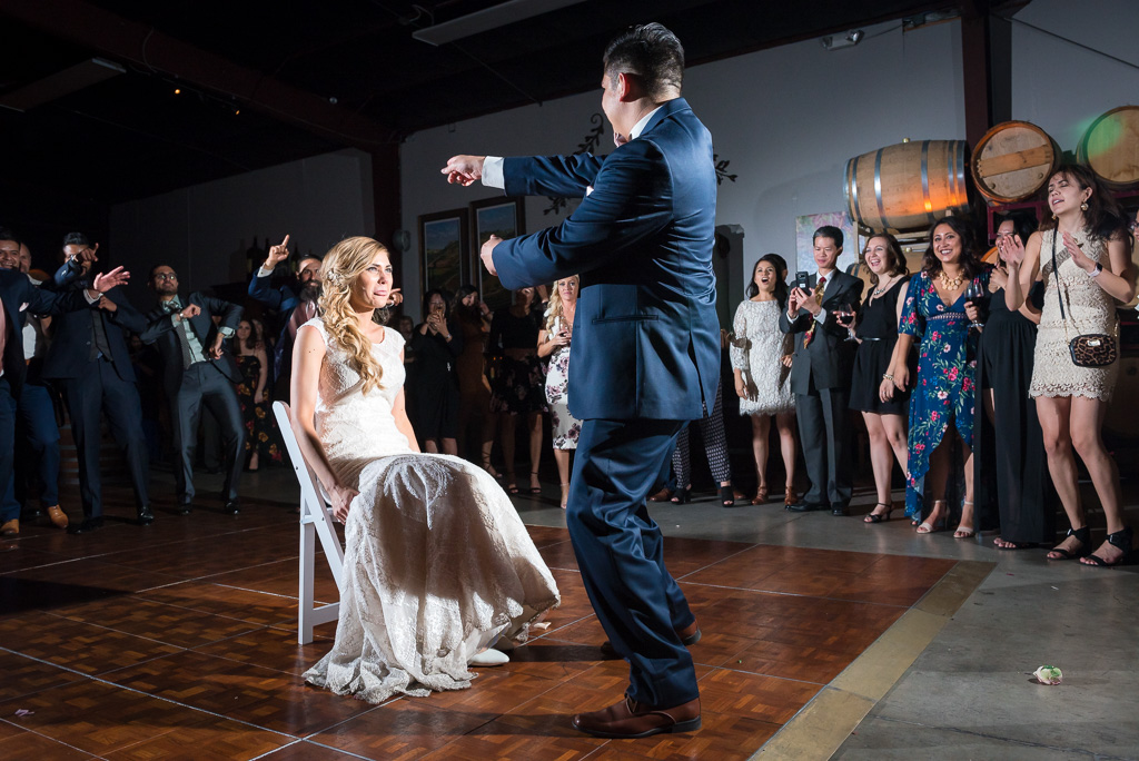 A groom prepares to remove his bride's garter.