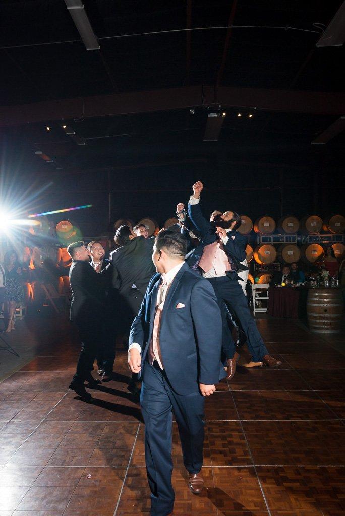 A garter toss photo at a barrel room wedding reception.