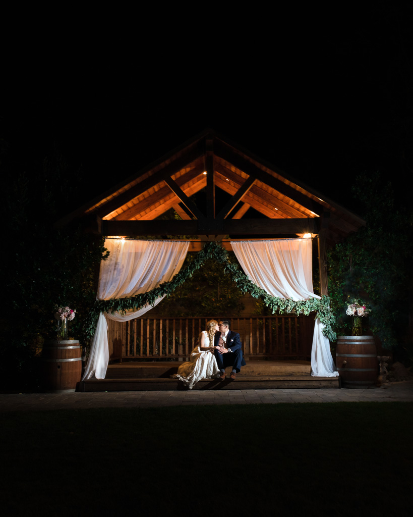 A bride and groom sit inside the veranda at the Crooked Vine Winery, where they were married just hours earlier.