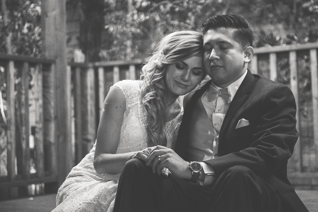 Black and white photograph of a bride and groom resting, cuddling.