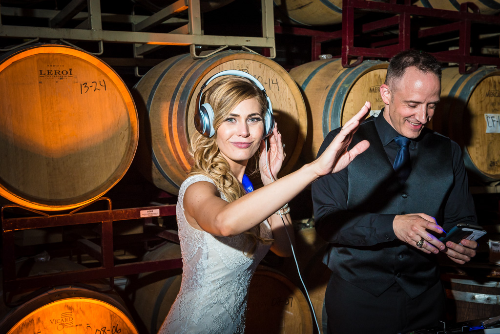 A bride dons a pair of headphones pretending to be a DJ.