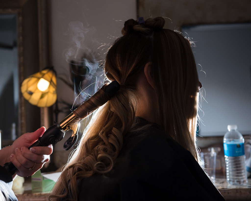 Photograph of a bride backlit while having her hair curled.