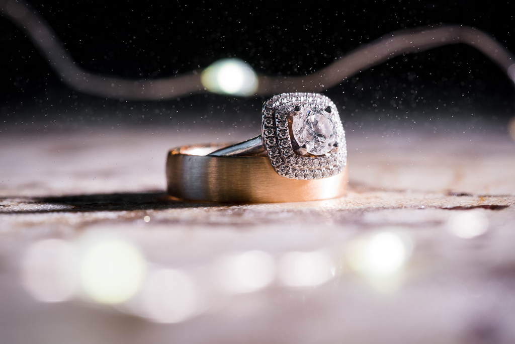 Stylistic photograph of a wedding ring and engagement band with water droplets.