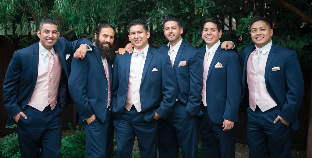 Ethnically diverse groomsmen pose in blue suits in front of a background of foliage.