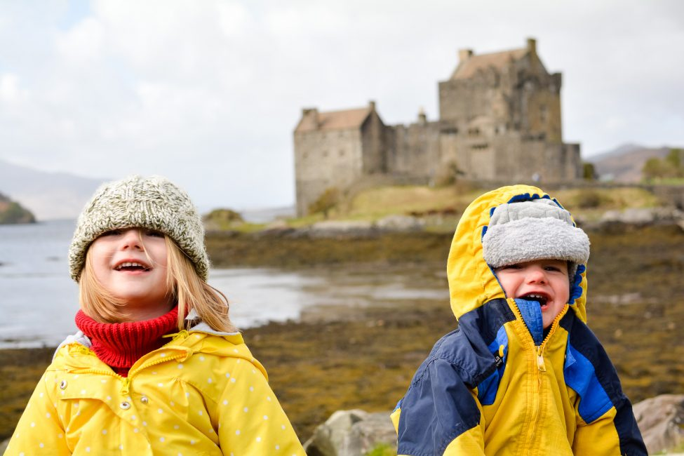 Two little children with Eilean Donan Castle in the background.