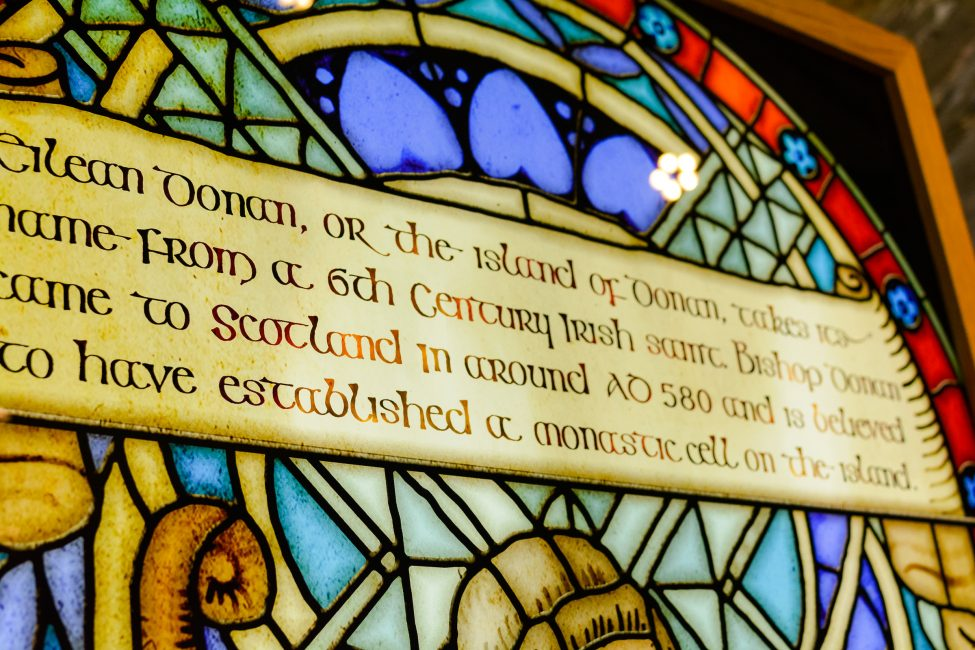 A stained-glass window telling the story of Eilean Donan Castle.