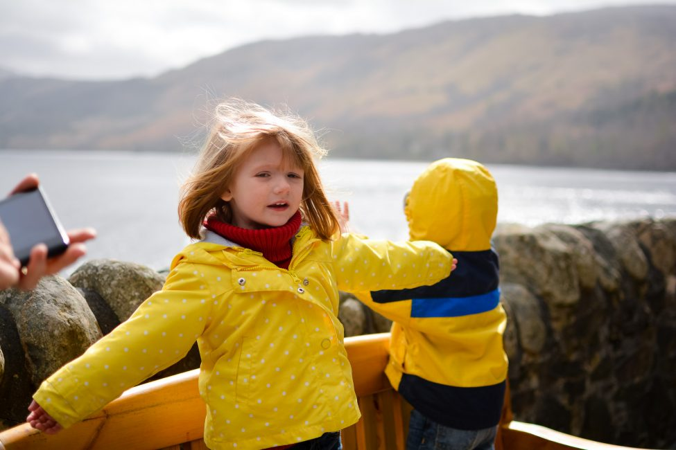 A young girl pretends to be queen on the parapets of Eilean Donan Castle.